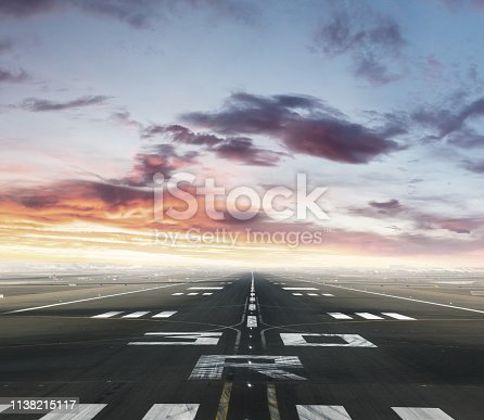 Empty airport runway. Concept of modern and fastest mode of transportation. Dramatic sunset sky on background