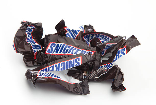 empty and crumpled snickers chocolate bars - kit kat stock photos and pictures