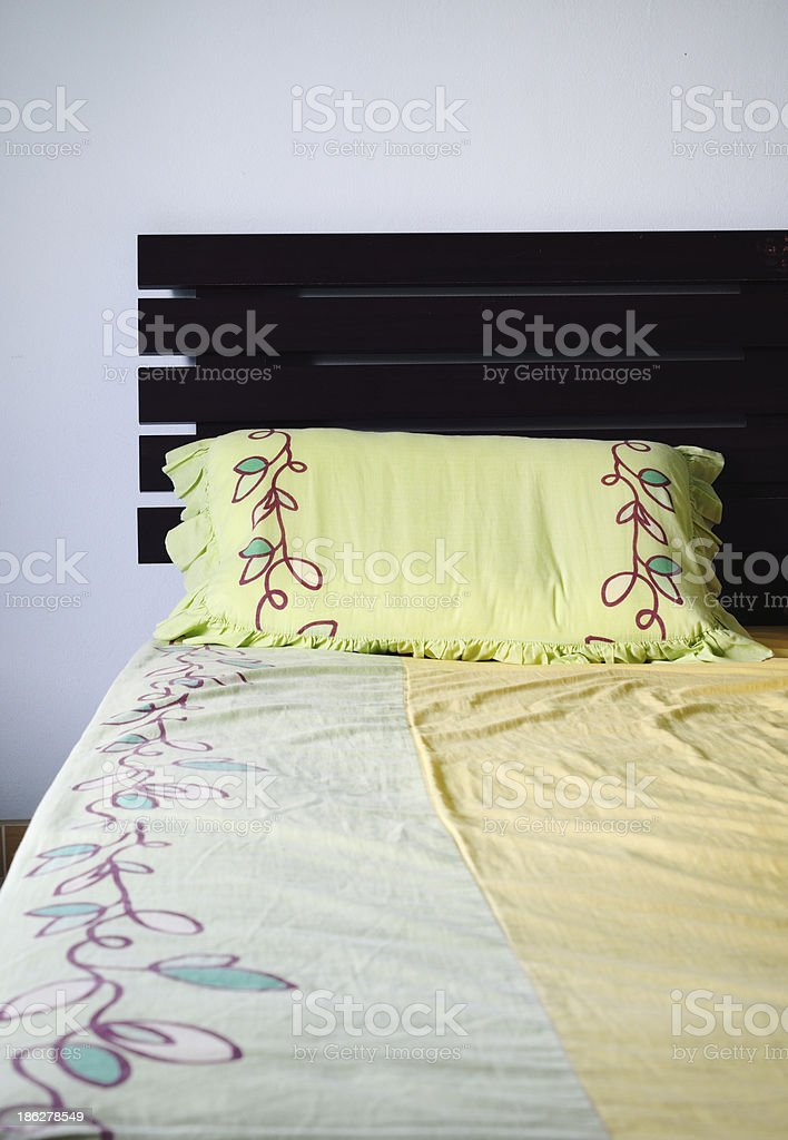 Empty and messy bed with green pillow, royalty-free stock photo