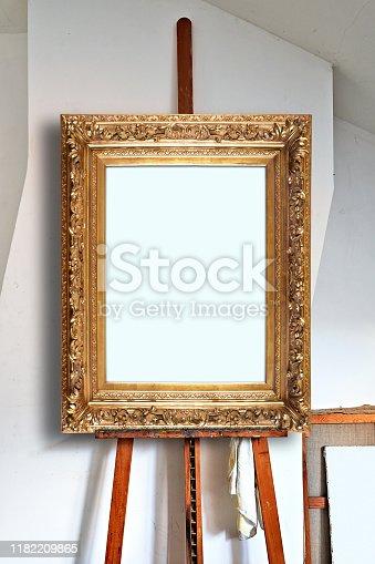 671393252 istock photo empty antique golden frame in an artist's studio 1182209865