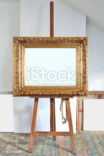 671393252 istock photo empty antique golden frame in an artist's studio 1182210096