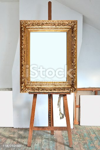 671393252 istock photo empty antique golden frame in an artist's studio 1182210153