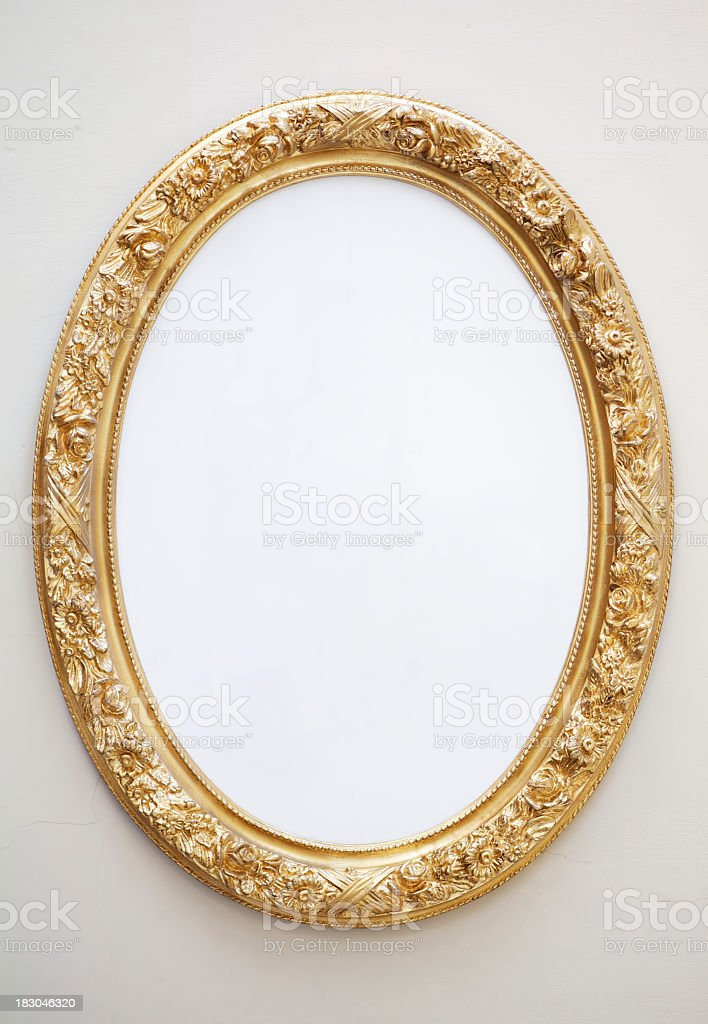 Empty Antique Mirror in Gilt Oval Frame on Neutral Wall royalty-free stock photo