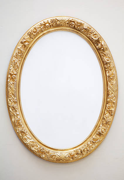 Empty Antique Mirror in Gilt Oval Frame on Neutral Wall stock photo