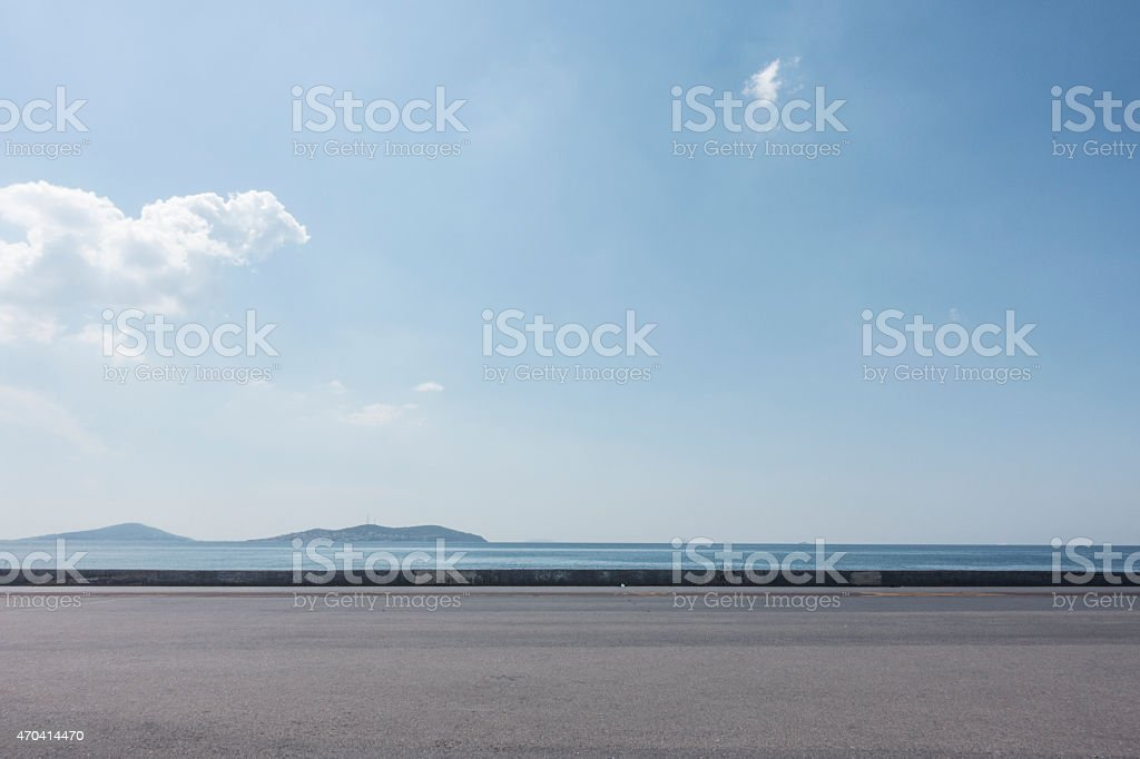 Empty asphalt lot with seaside background on a sunny day stock photo