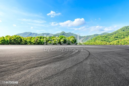 Asphalt race track ground and green mountains natural landscape