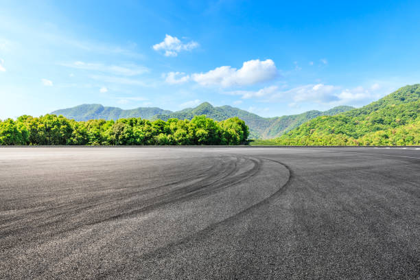 Empty asphalt race track and green mountains natural landscape Asphalt race track ground and green mountains natural landscape horizon over land stock pictures, royalty-free photos & images
