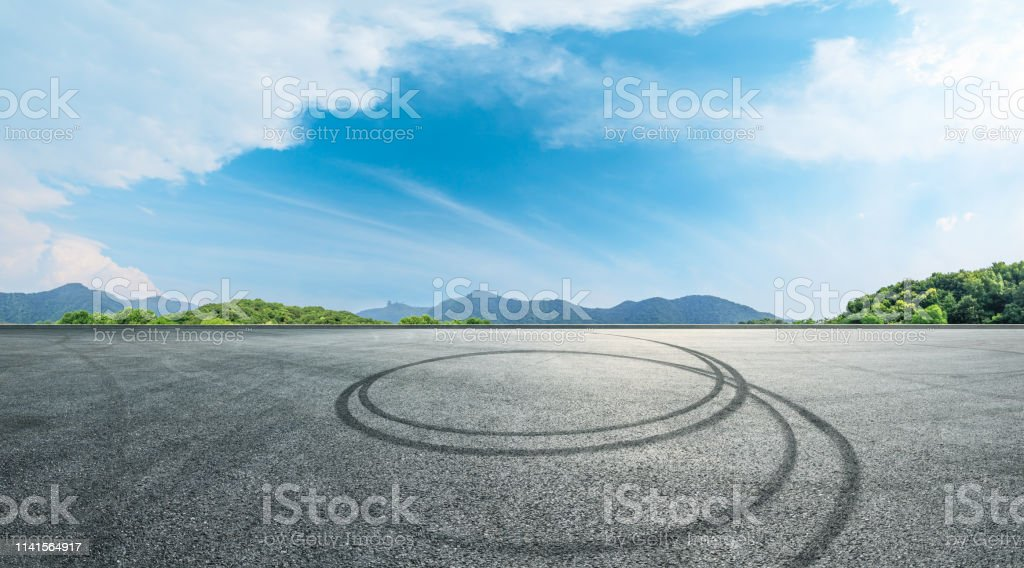 Asphalt race track ground and mountains with blue sky landscape