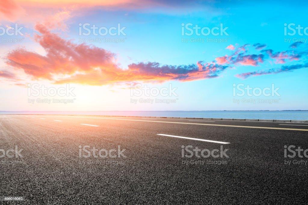 empty asphalt road and blue sea nature landscape at sunset stock photo