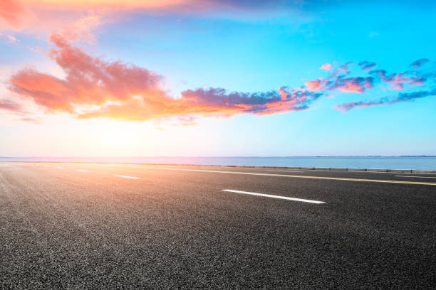 empty asphalt road and blue sea nature landscape at sunset stock photo