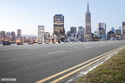 860403416istockphoto empty asphalt road and cityscape of modern city in blue sky at dawn 847315428