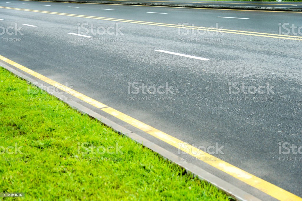 Empty asphalt road and green field