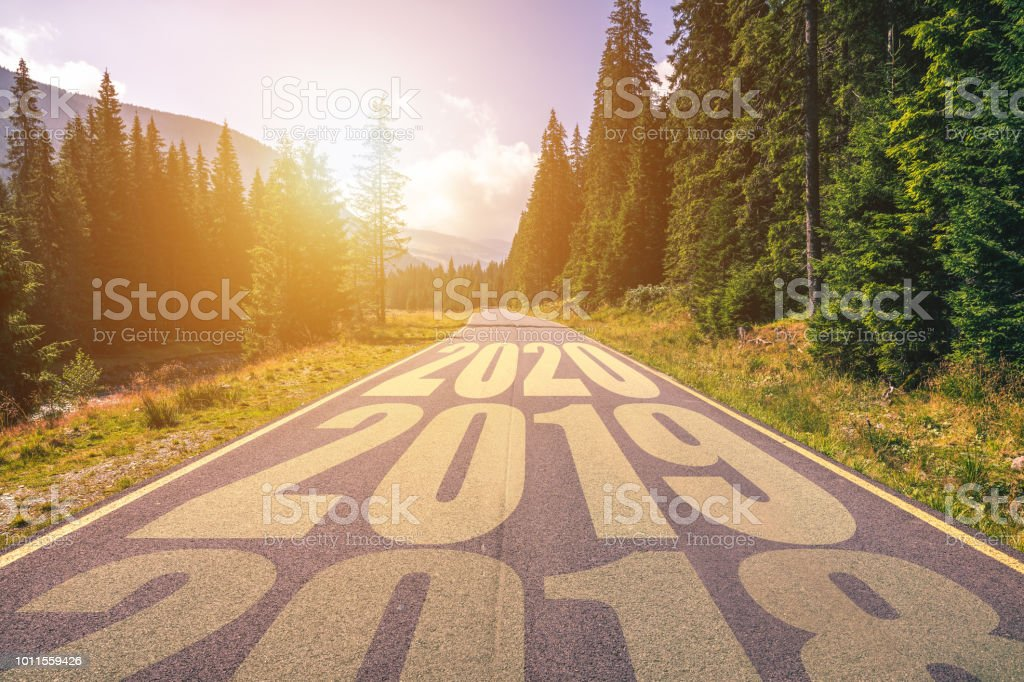 Empty asphalt road and New year 2018, 2019, 2020 concept. Driving on an empty road in the mountains to upcoming 2018, 2019, 2020 and leaving behind old years. Concept for success and passing time. royalty-free stock photo