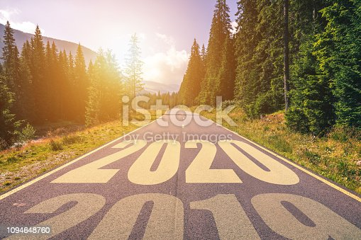 1170070487 istock photo Empty asphalt road and New year 2020 concept. Driving on an empty road in the mountains to upcoming 2020 and leaving behind old 2019. Concept for success and passing time. 1094648760