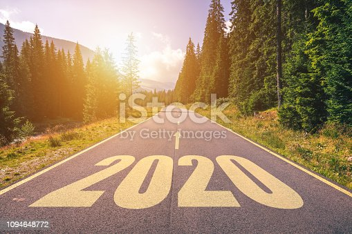 1170070487 istock photo Empty asphalt road and New year 2020 concept. Driving on an empty road in the mountains to upcoming 2020 and leaving behind old 2019. Concept for success and passing time. 1094648772