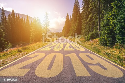 1170070487 istock photo Empty asphalt road and New year 2020 concept. Driving on an empty road in the mountains to upcoming 2020 and leaving behind old 2019. Concept for success and passing time. 1178972721