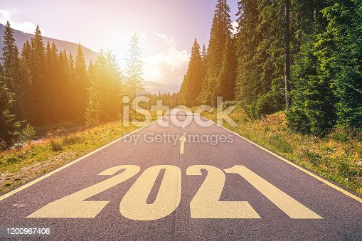istock Empty asphalt road and New year 2021 concept. Driving on an empty road in the mountains to upcoming 2021 and leaving behind old 2020. Concept for success and passing time. 1200967406