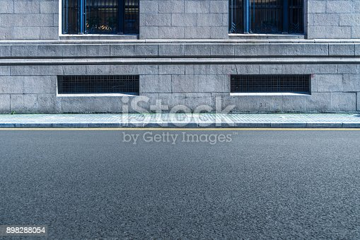 istock empty asphalt road front of the wall 898288054