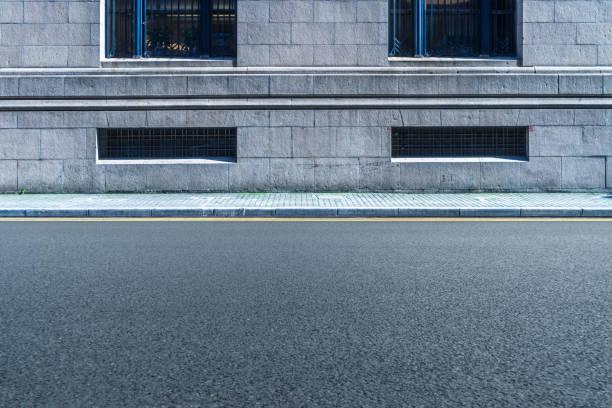 壁の空アスファルトの道の前部 - 歩道 ストックフォトと画像