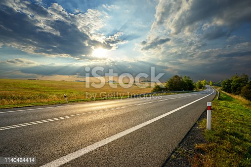 Empty asphalt road in rural landscape at sunset with dramatic clouds