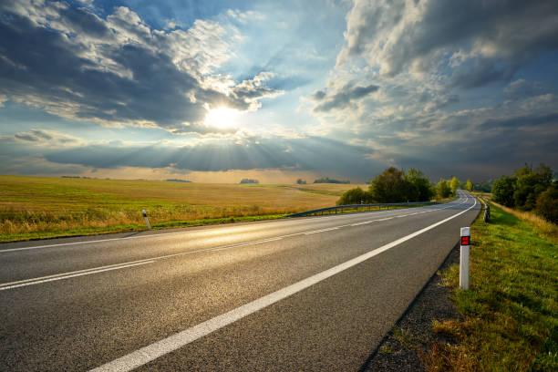 carretera asfaltada vacía en el paisaje rural al atardecer con nubes dramáticas - vía fotografías e imágenes de stock
