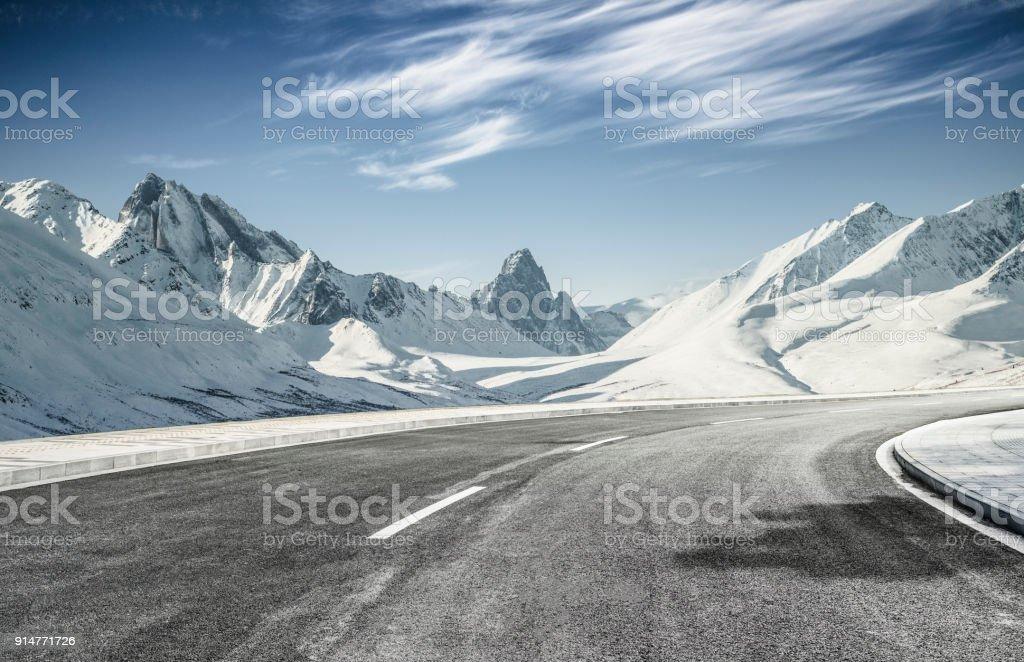 雪の山に向かって空アスファルト道 ストックフォト