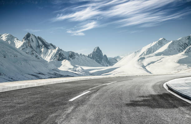 empty asphalt road leading towards snow mountains - estrada imagens e fotografias de stock