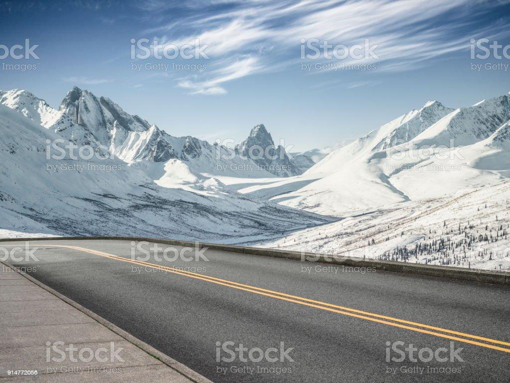 leere asphaltierte Straße in Richtung Schneeberge – Foto