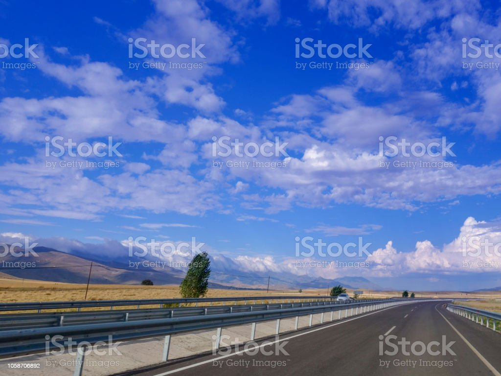 Empty asphalt road to the background blue sky