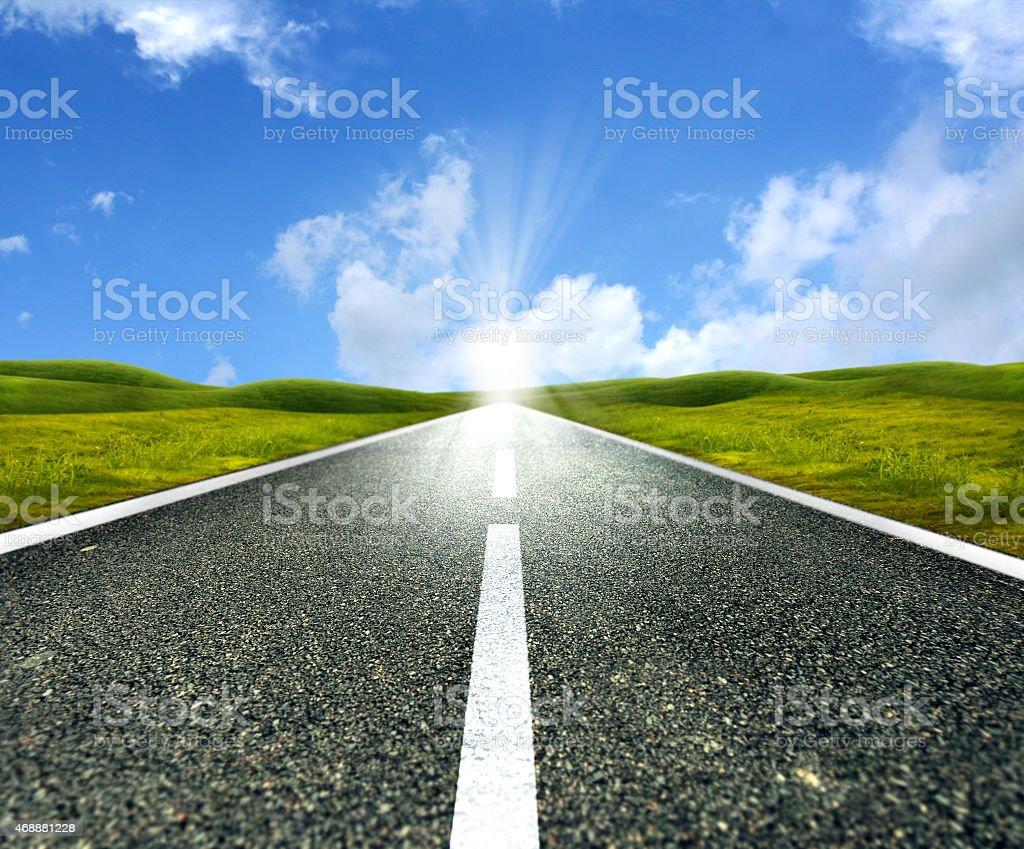 Empty asphalt road towards bright sun stock photo