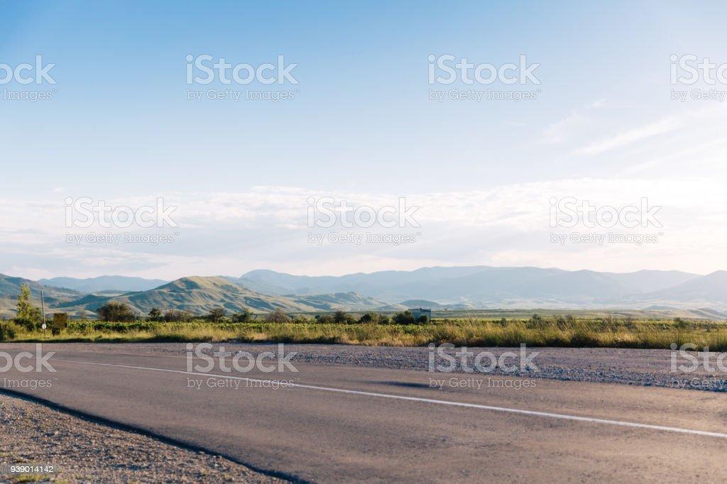 Leere Asphaltstraße mit blauen Sommerhimmel und Hügeln im Hintergrund. Krim, Koktebel. – Foto