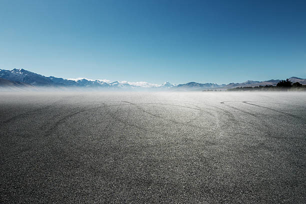 empty asphalt road with car tracks with snow mountains stock photo