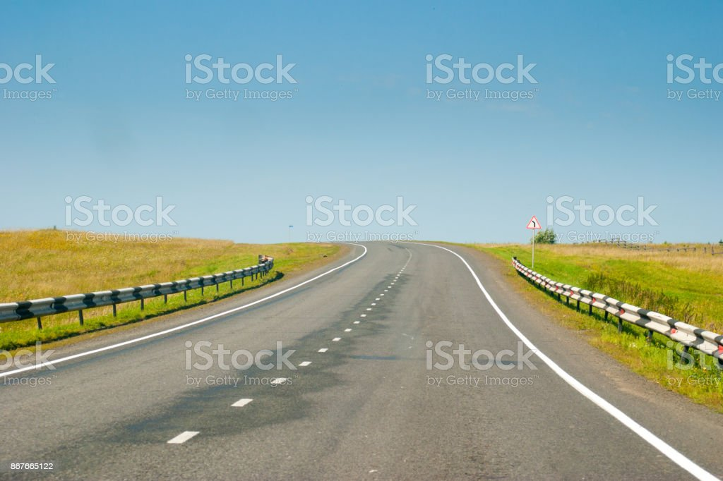 empty asphalt road with turn warning road sign stock photo