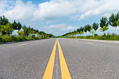 Empty asphalt road with yellow stripes.