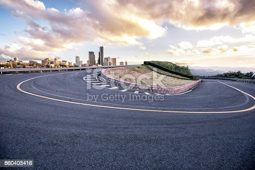 istock empty asphalt sharp turn with modern city 860403416