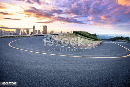 860403416istockphoto empty asphalt sharp turn with modern city 860877566