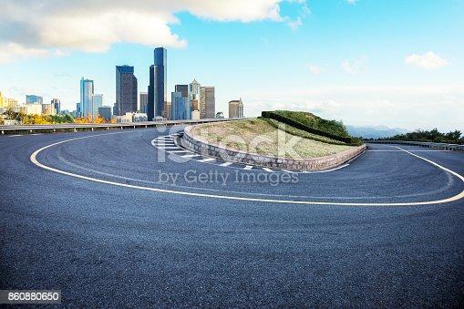 860403416istockphoto empty asphalt sharp turn with modern city 860880650