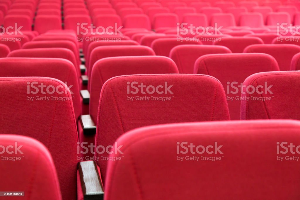 Rows of red seats in an empty concert hall