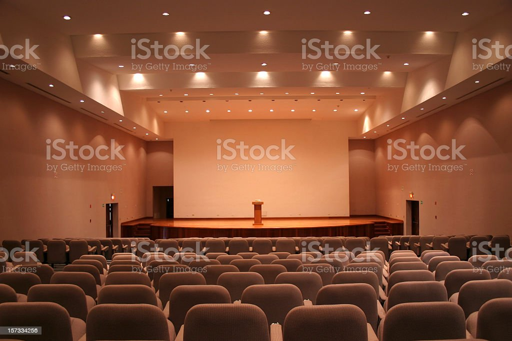 Empty auditorium with grey seats and downlights stock photo