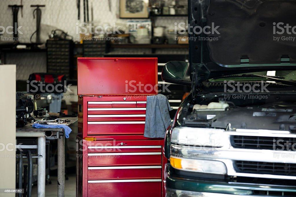 Empty automobile repair shop. Toolbox, vehicle with hood open. stock photo