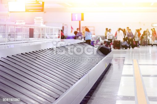 istock empty baggage conveyor belt at the airport with blurred waiting passenger background 928192092