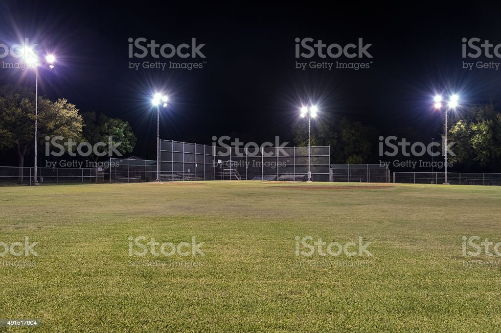Empty baseball field at night with the lights on stock photo