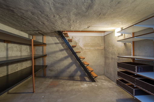istock empty basement in abandoned old industrial building with little light and a wooden stairs 967942518