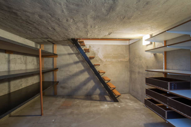 empty basement in abandoned old industrial building with little light and a wooden stairs - basement stock pictures, royalty-free photos & images
