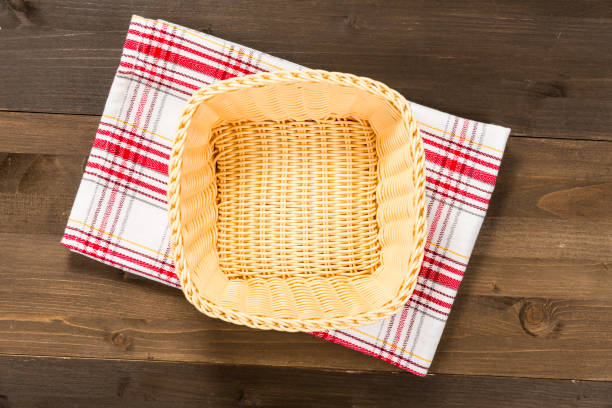 Empty basket with checkered tablecloth on a wooden background stock photo