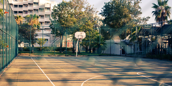 empty basketball court behind metal fence in early morning time outside