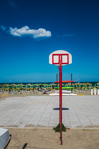 Empty basketball court on sea against blu sky.