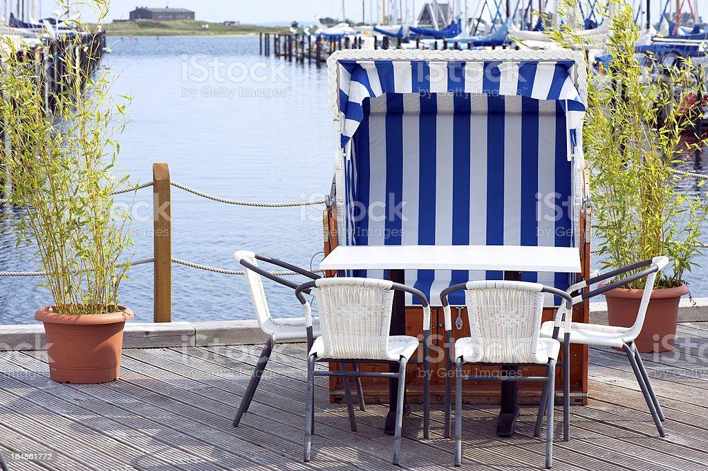 Empty beach chair on the yacht harbor stock photo