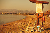Rear view of a lifesaver station with two chairs and a preserver rings hanging. The empty and peaceful Egyptian beach can be seen during sunrise.