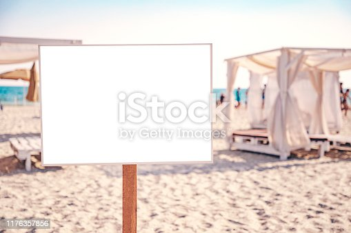 Empty beach sign board mock up. Copy space for your text or image. White sand, blue sea and people on the background